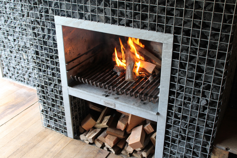 Steinkorb Kamin Grill mit Feuer